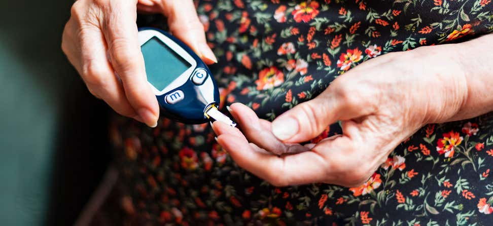 A senior woman is monitoring her glucose levels.