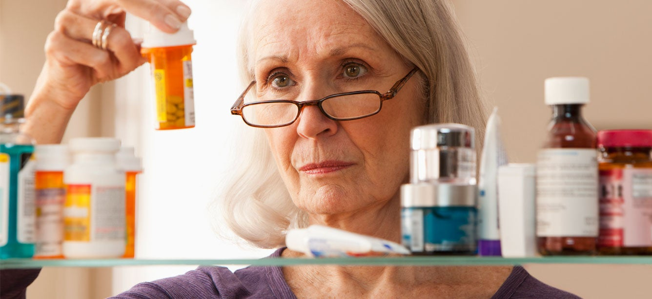 A senior woman is looking at prescription bottles in her bathroom.