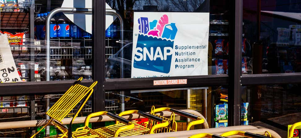 "A ""We Accept Supplemental Nutrition Assitance Program (SNAP)"" sign appears on the window of a grocery retailer."