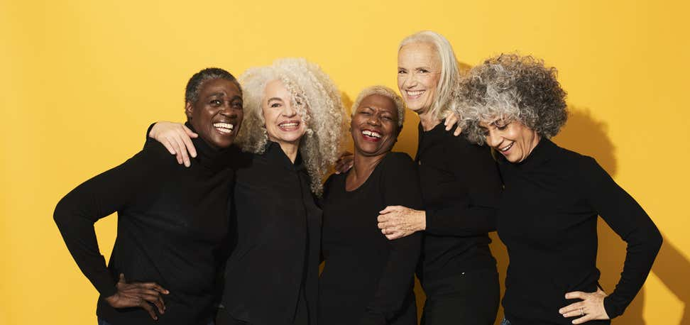 A group of senior women pose for the camera, wearing all black and smiling - with a yellow backdrop.
