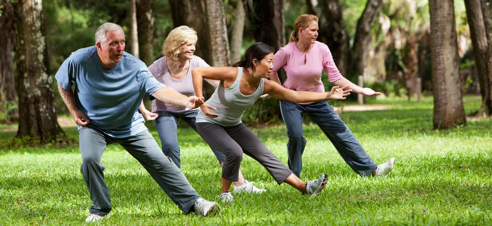 Three seniors and an instructor practice tai chi in a park.