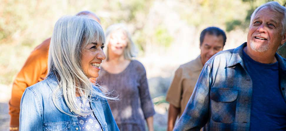 A group of older adults is walking outside, enjoying nature and laughing/smiling.