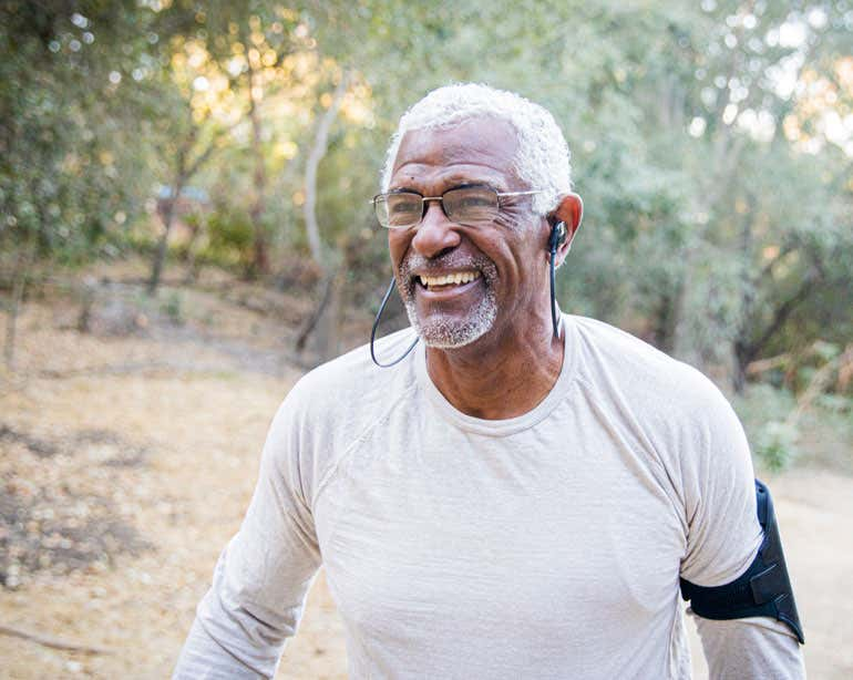 A Black senior man is exercising outside, wearing his phone on his arm and with his earbuds in.