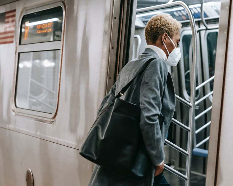 An older Black professional woman is seen getting on the subway.