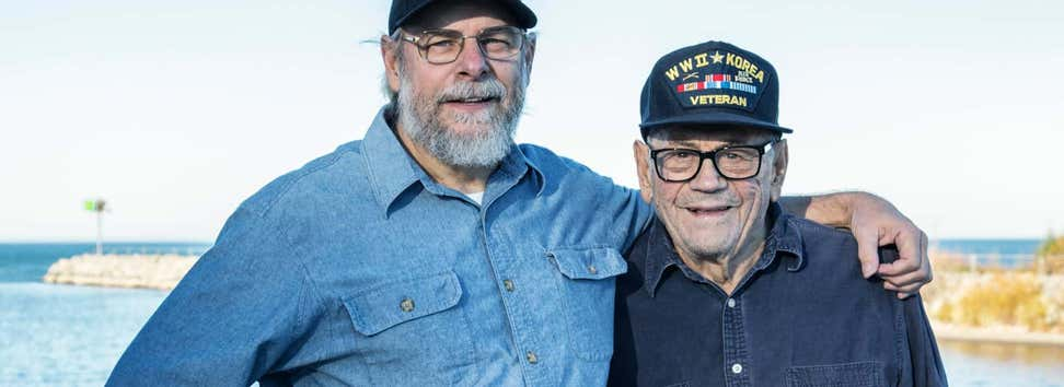 Two elder Vietnam veterans are embracing each other by the shore.