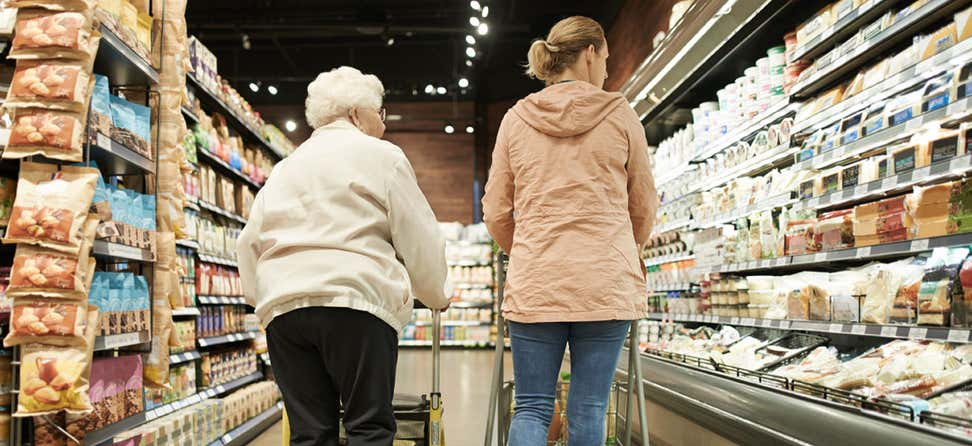 A senior Caucasian woman and her female caregiver are shopping for groceries.