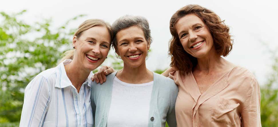 Three older women are outside posing for the camera, smiling.