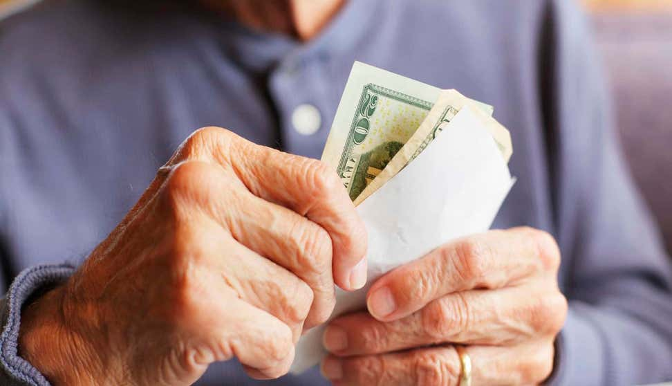 Older woman's hands holding cash in an envelope.