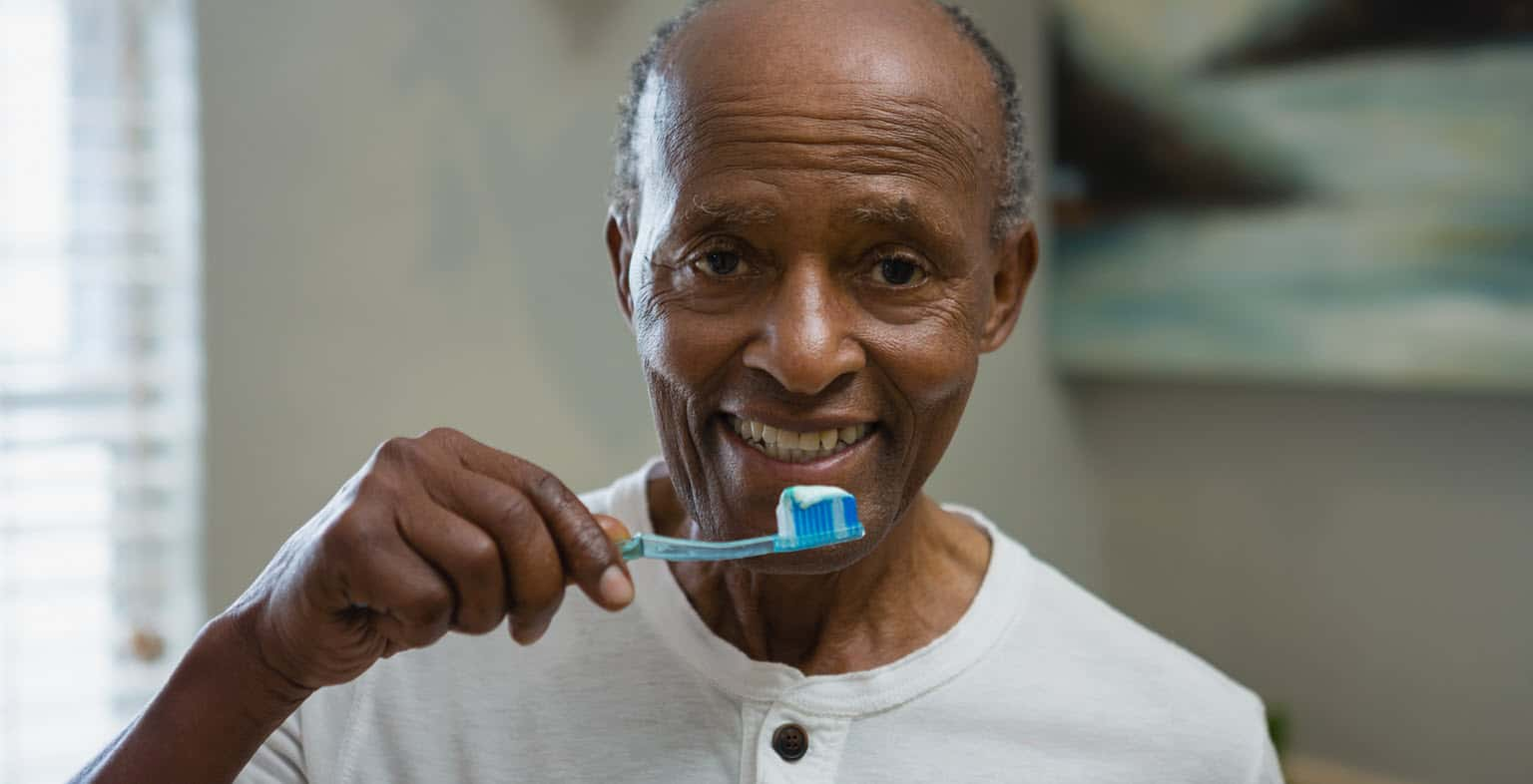 A senior Black man holds up a toothbrush as though he's ready to brush his teeth.
