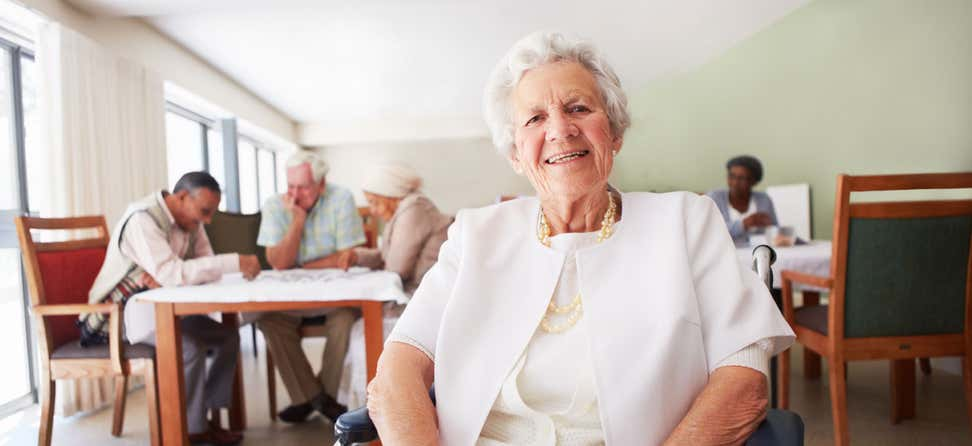 An older woman smiles while sitting in a room with other seniors at a senior center.