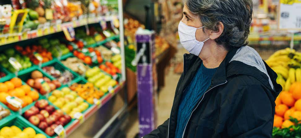 A senior woman with dark, short hair and wearing a mask is in the produce section of a grocery story contemplating what to buy.