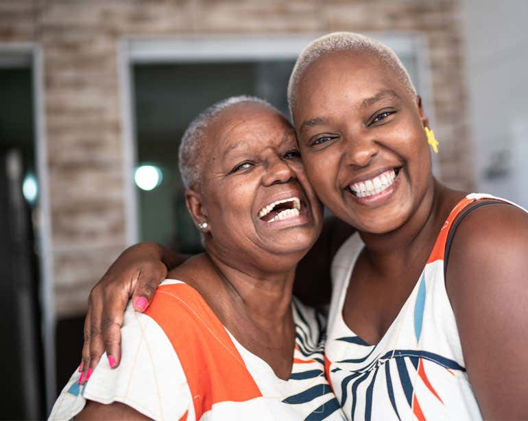 A Black senior woman embraces her daughter, both laughing and smiling beautifully.