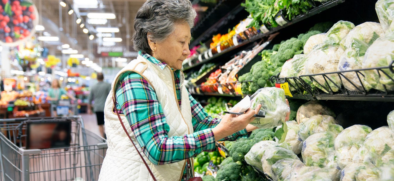 A senior Asian woman is looking at produce in the grocery store.