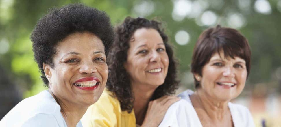 Three multi-ethnic women pose for the camera, all smiling.