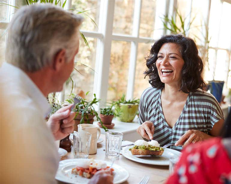A middle-aged woman is enjoying her brunch with her father, laughing during their conversation.