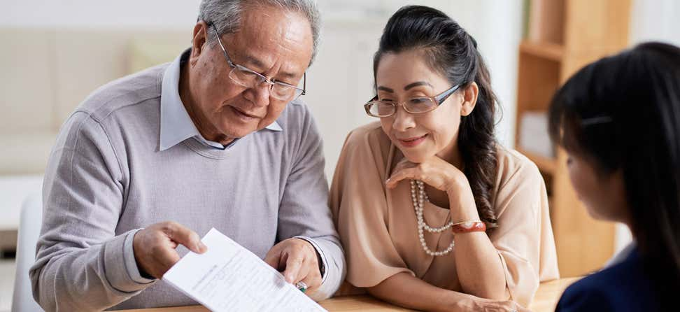 A senior Asian couple is looking over a financial document with their benefits enrollment advisor.