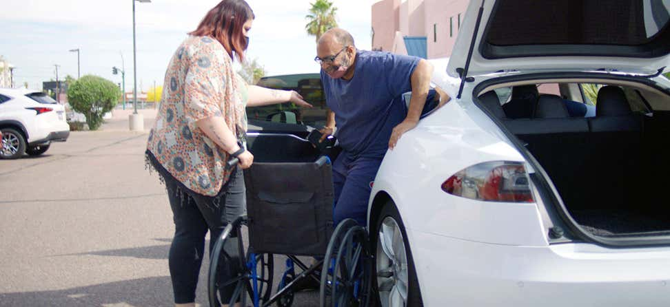 A Lyft driver helps a senior man get out of the car and into a wheel chair at a COVID-19 vaccine event in Arizona.