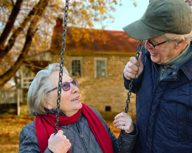 A senior Caucasian man looks down lovingly at his wife while she's swinging outside.