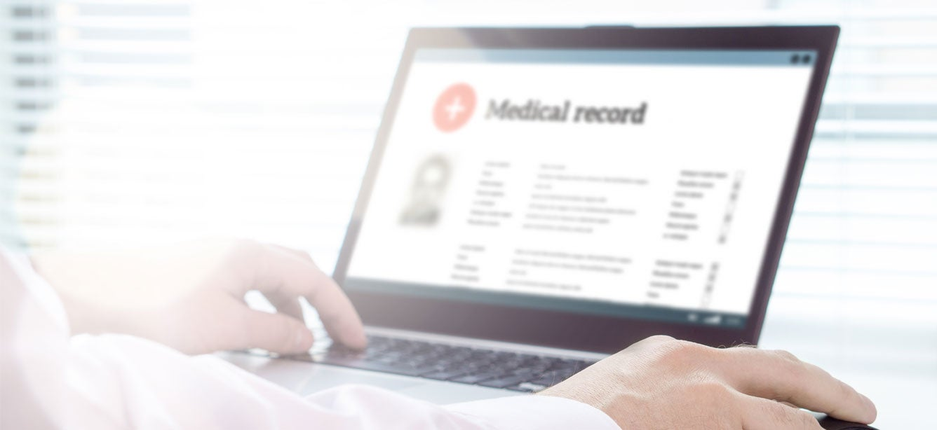 An up close shot of a laptop screen that has a generic medical record on display.