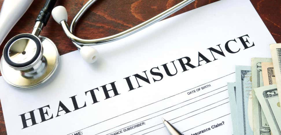 Form with health insurance written at top and stethoscope with dollar bills.