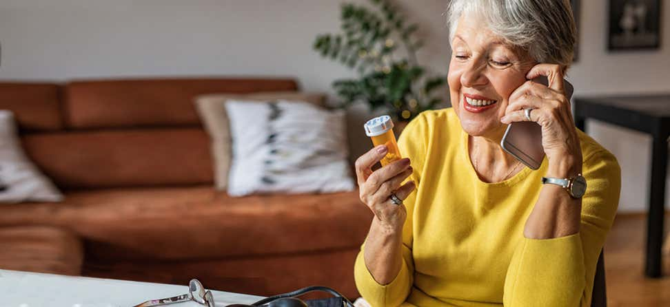 A senior woman wearing a yellow shirt is holding a prescription bottle in her hand while on the phone.