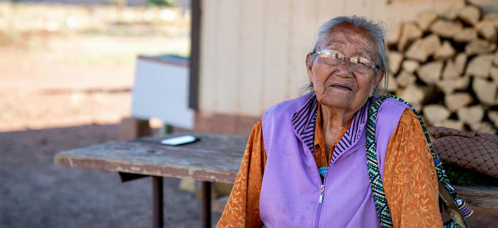 A senior Navajo, American Indian woman is looking at the camera solemnly.