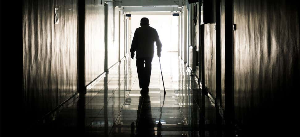 A disabled man using a cane is seen leaving a nursing home.