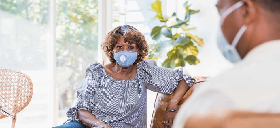 A senior Black older woman with blue mask is seated on a couch, talking to her mental health provider.