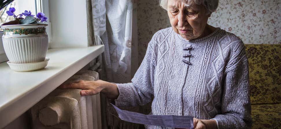 A senior woman places her hand on her heater/radiator while looking at her electricity bill.