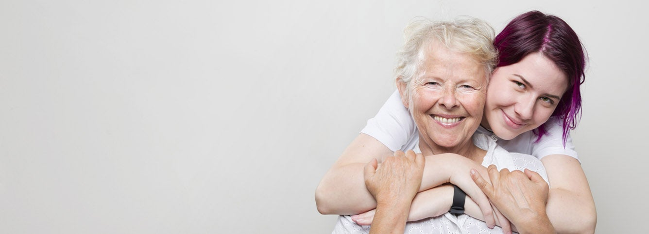 A senior woman is smiling while her younger female caregiver embraces her with a hug from behind.