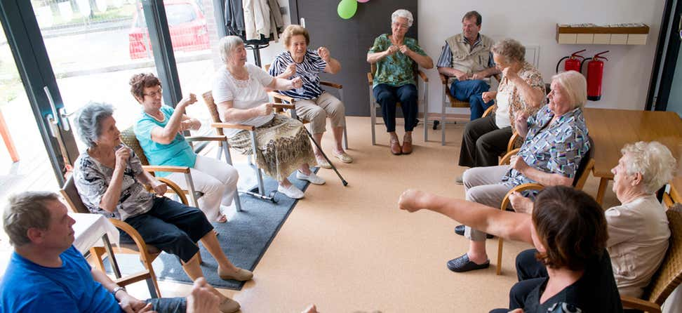 A group of seniors are doing exercises while seated at a senior center.