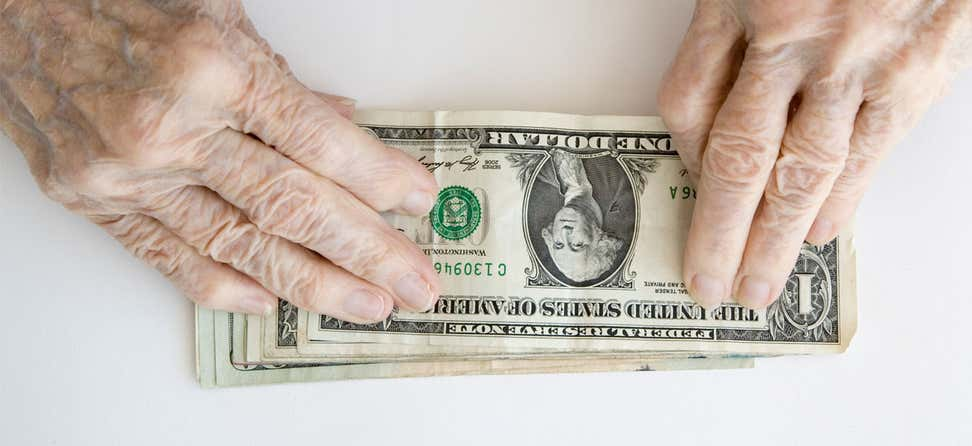Older/senior hands are placed on top of a stack of one dollar bills.