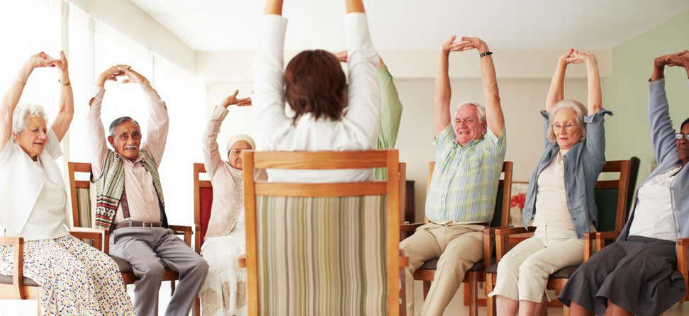 A group of older adults are going through their daily stretching exercise routine at a senior center.
