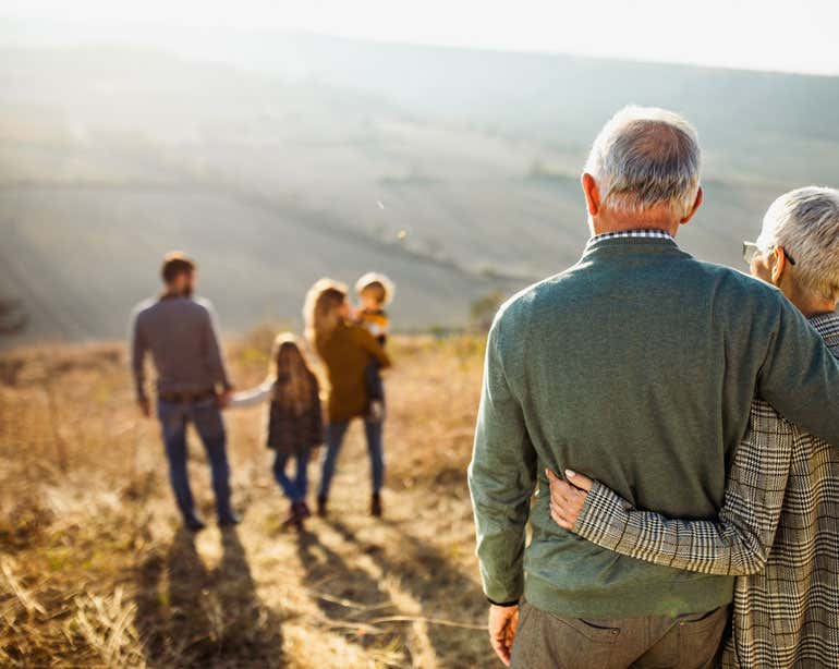 A senior couple hugs at the top of a hill, looking down at their family walking together.