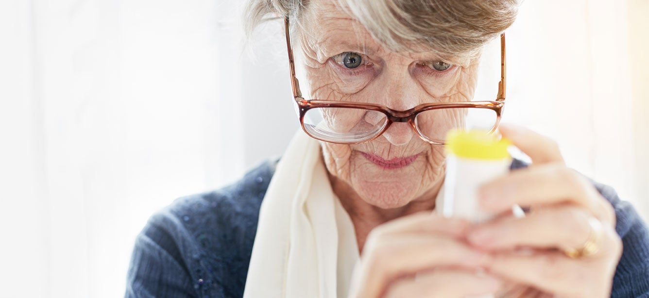 Senior woman peers through her glasses, trying to read instructions on a prescription bottle.