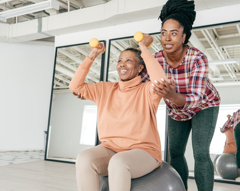 Black woman sitting on exercise ball in gym with hand weights and physical therapist helping her