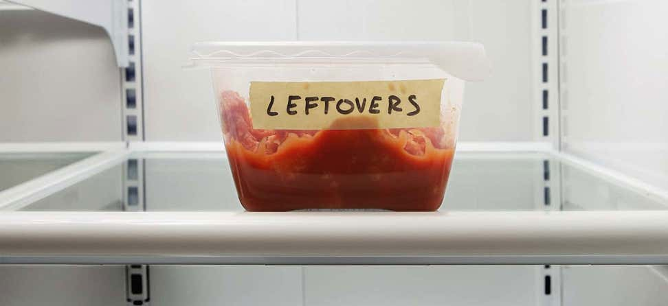 "Closeup shot of a food container in a fridge that is labeled as ""leftovers"" with masking tape."