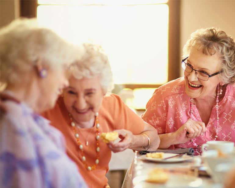 Three senior Caucasian women are laughing while enjoying a meal at a senior center.