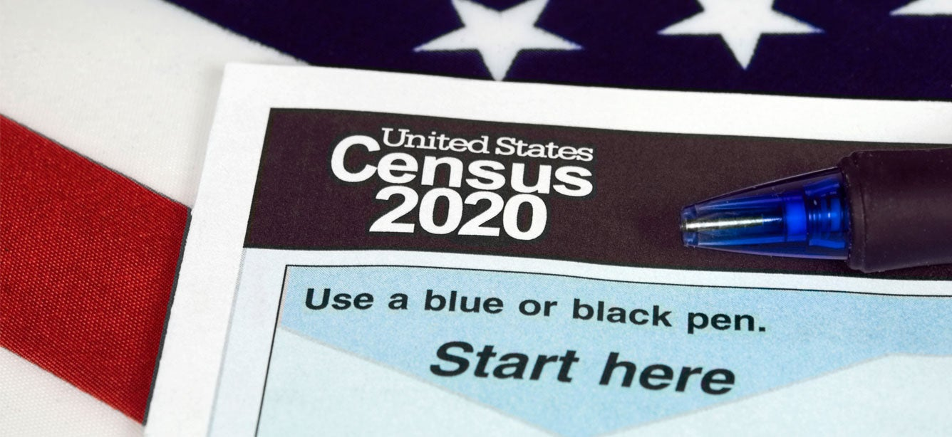 A close up shot of a U.S. Census 2020 form with a U.S. flag as the backdrop.