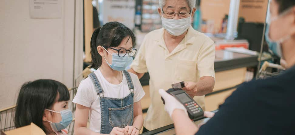 Senior Asian man is paying at the grocery register with his two granddaughters, while all are wearing their masks during the pandemic.