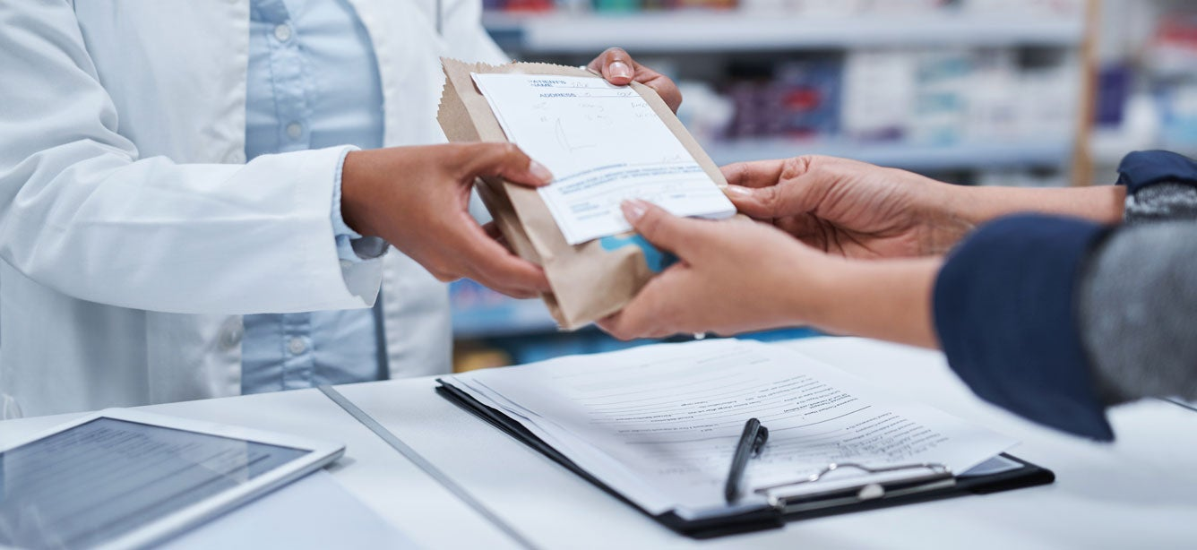 A closeup shot of a pharmacist assisting a customer with their prescription.