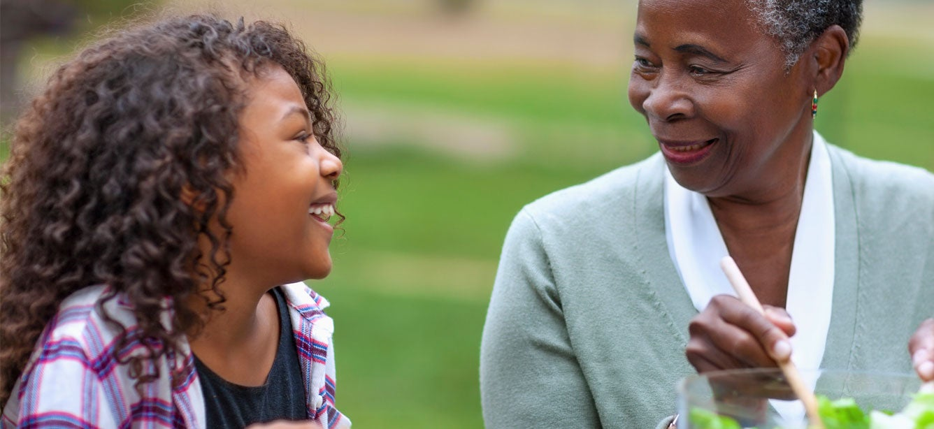 A Black senior woman and her granddaughter are sitting outside at a picnic table enjoying a salad together and laughing.