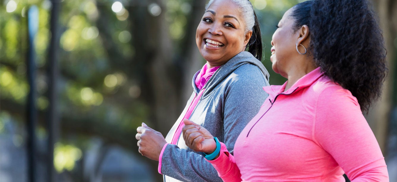 Two Black senior women are out exercising while smiling and talking to each other.