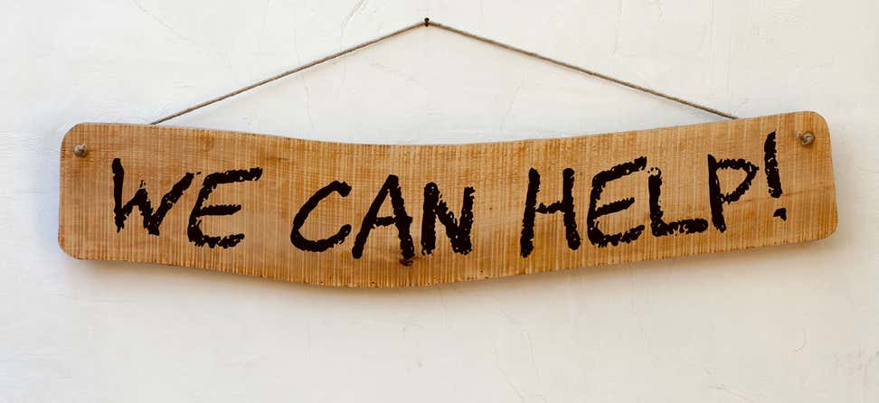 "A hanging wooden sign with the phrase ""We can help!"" written on it."