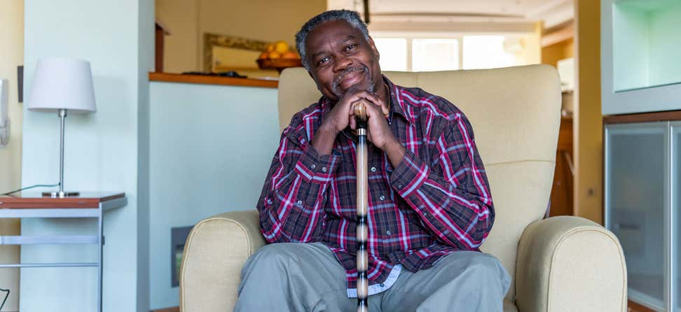 A Black senior man is sitting at home in a comfortable chair, smiling.