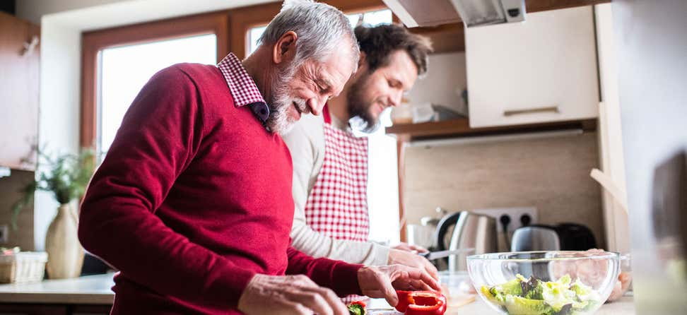 An older man and his son are cooking together in the kitchen, both smiling and enjoying each other's company.