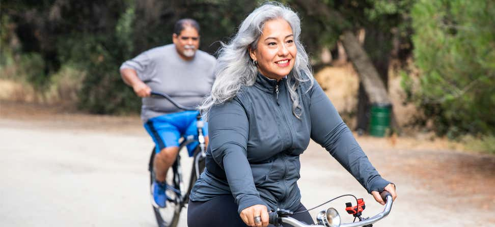 A senior Hispanic couple is outside biking together in nature.