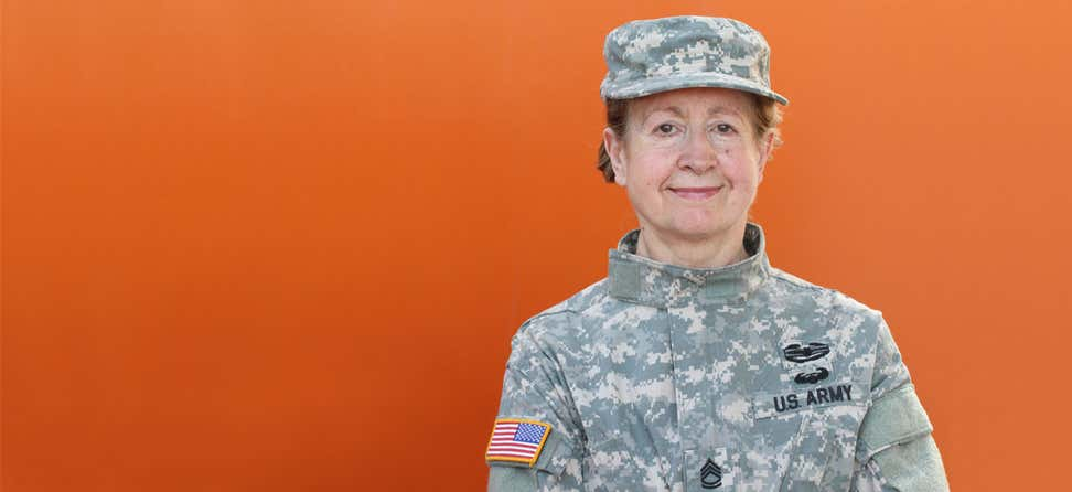 An older female veteran is posing for the camera, smiling.