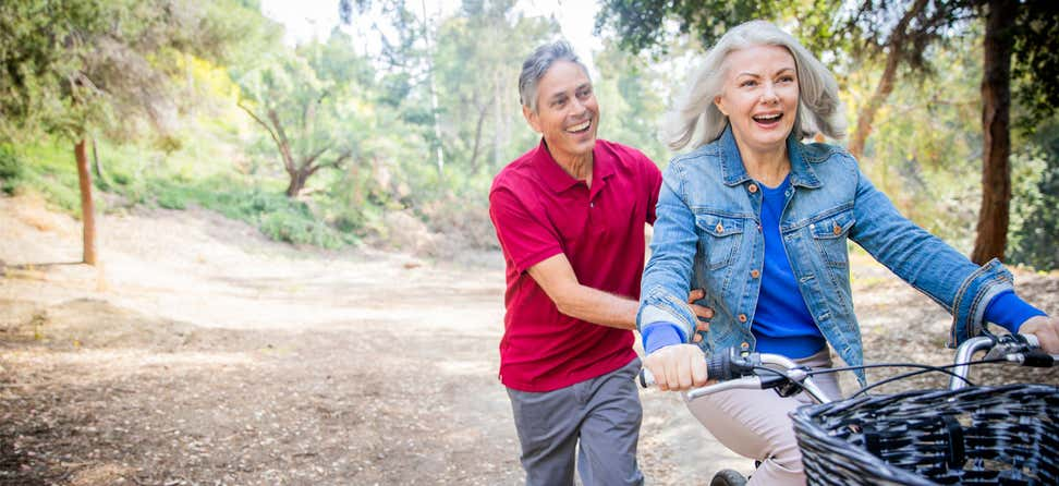 An older woman is being pushed by her husband while riding her bike outside in nature.