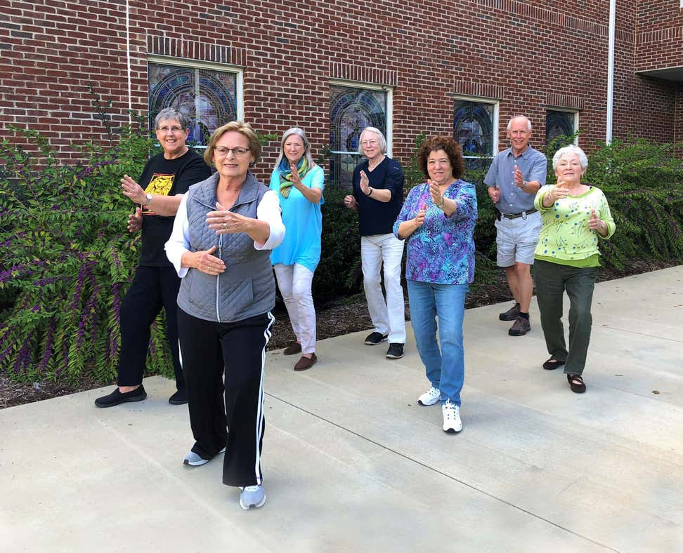 A group of older adults is outside practicing Tai Chi. (Image by Nicole Hiegl)